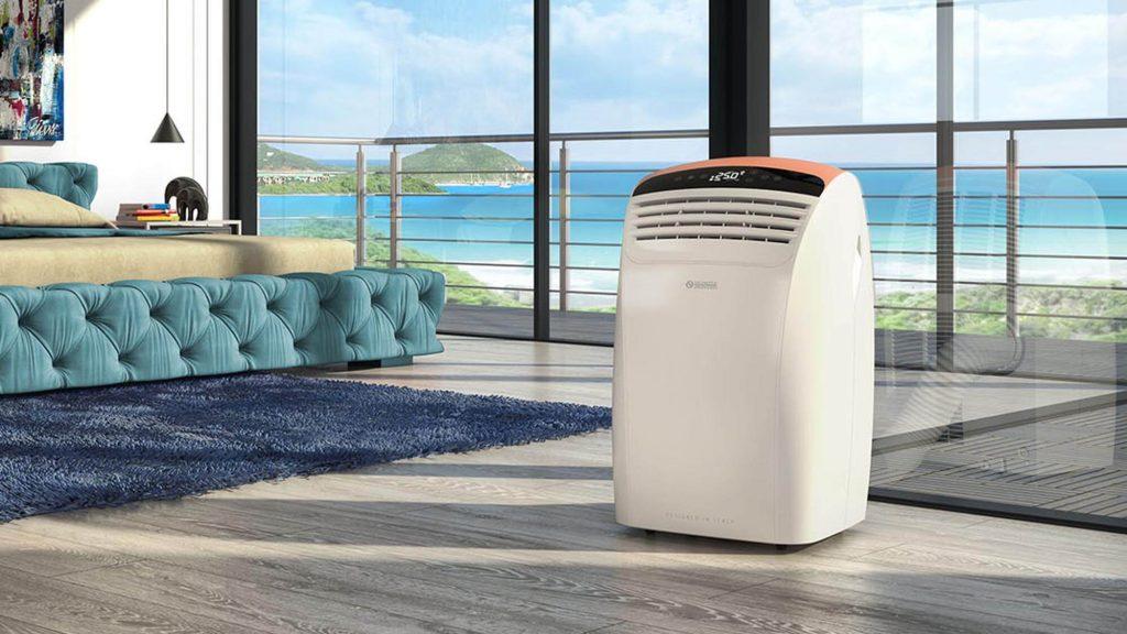 Ar condicionado portátil em um quarto com janela de vista ao mar azul.